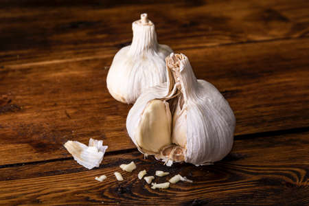 Two garlic cloves on a wooden board in soft side light