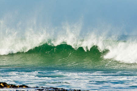 large braking wave with sea spray from a strong off shore wind on a hot summers day