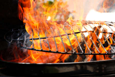 Hot orange flames burning a steel grid filled with fat and leftover meat from a braai or barbeque