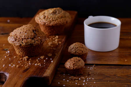 freshly baked bran muffins on a wooden board with a cup of black coffee in the background