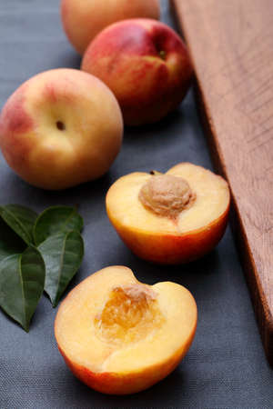 soft juicy,ripe  peaches sliced in half ready to be eaten on a grey background