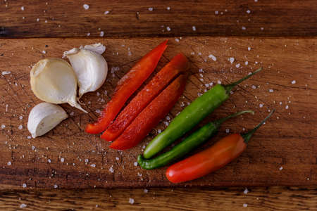 Garlic and chillies on a wooden board with added spices for cooking and seasoning food