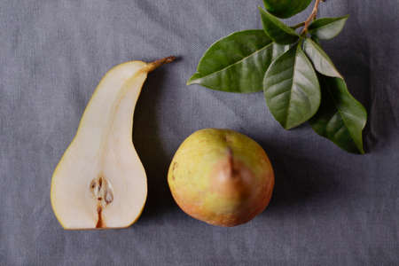 sliced fresh juicy pear with fresh green leaves on a grey cloth in soft window light