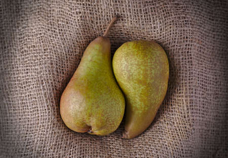 two juicy pears together in a cuddling shape on burlap or Hessian material Stock Photo