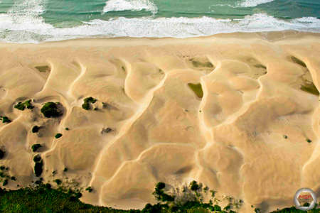 Beautiful side lit sand dunes running into the sea crafted by high winds and sand erosion Reklamní fotografie