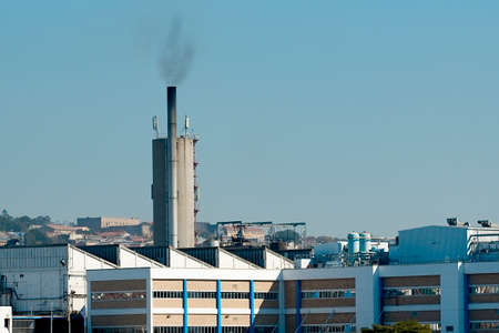 Large factory in an urban area with a tall chimney creating climate warming and pollution