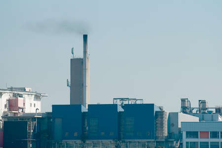 Large dirty chemical Factory in an urban area creating smoke from a tall chimney 版權商用圖片