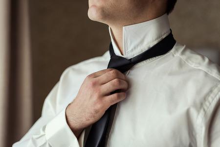 Las personas, los negocios, la moda y la ropa concepto - cerca del hombre en camisa de vestir y ajusta el lazo en el cuello como en casa. El hombre de negocios pone en un empate. Hombre que pone en la corbata. El hombre de negocios de vestirse por la mañana Foto de archivo