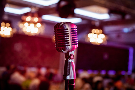 Microphone. Retro microphone. A microphone on stage. A pub. Bar. Restaurant. Classic. Evening. Night show. European restaurant. European bar. American restaurant. American bar.