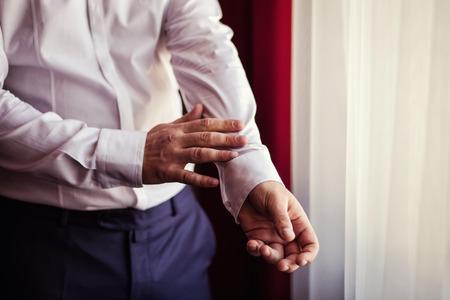 cufflink: Businessman dress shirt. Politician, mans style, Businessman buttoning his shirt,male hands closeup, American, European businessman