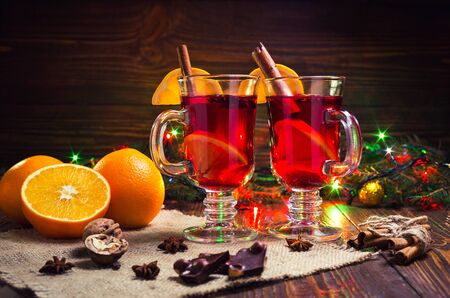 Two glasses,cup of red hot drink.Mulled wine on wooden background with christmas spices,orange slice,close up.Christmas mulled wine.Branch of Christmas tree, Christmas lights