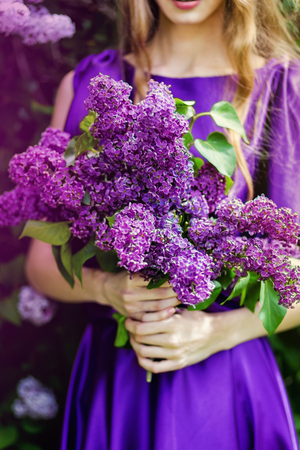 Beautiful girl in a purple dress and a bouquet of lilacs. Beautiful girl in a pink dress standing in the garden lilac bushes. The model is in image of spring. Stock Photo