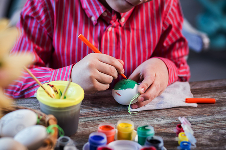 eastertime: colouring eggs for eastertime at home.Happy easter! A mother and her son painting Easter eggs. Happy family preparing for Easter.decorating Easter eggs, childrens hands hold a paintbrush and paint