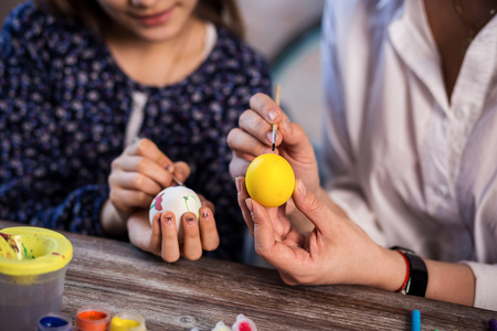 eastertime: colouring eggs for eastertime at home.Happy easter! A mother and her daughter painting Easter eggs. Happy family preparing for Easter.decorating Easter eggs, childrens hands hold a paintbrush and paint