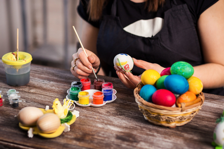 eastertime: colouring eggs for eastertime at home.Happy easter! A mother,girl painting Easter eggs. Happy family preparing for Easter.decorating Easter eggs, woman hands hold a paintbrush and paint Stock Photo