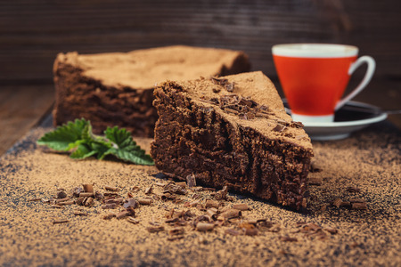 chocolate cake with Candies and cup of coffee,Chocolate cake with a cut piece and blade on gray background,closeup,Dark chocolate cake,vegan chocolate cake,Tasty chocolate cake on wooden background Stock Photo