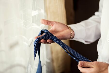 People, business, fashion and clothing concept - close up of man in shirt dressing up and adjusting tie on neck at home. Businessman putting on a tie. Man putting on necktie. Businessman getting dressed in the morning