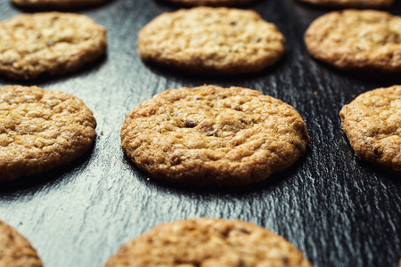 Biscuit sweet cookie background. Domestic stacked butter biscuit pattern concept,close up macro.Homemade cookies on wooden table.Cereal biscuits with the sesame,peanuts,sunflower and amaranth. Stock Photo