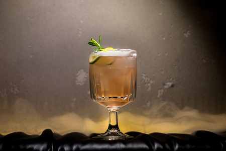 dark and stormy rum cocktail with Lime against background of smoke