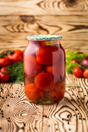 Marinated tomatoes with spices and ingredients on a wooden background