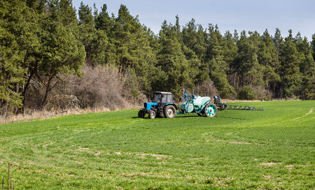 Tractor spraying insecticide to the green field, agricultural natural seasonal spring background