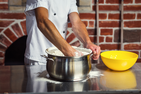 chef making dough for pizza. Man hands preparing bread. Concept of baking and patisserie