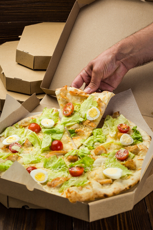 Pizza Caesar with chicken and tomatoes in box on wooden background Imagens