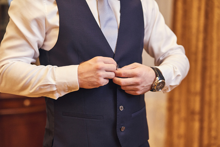 Businessman wears a jacket,male hands closeup,groom getting ready in the morning before wedding ceremony. Men Fashion Archivio Fotografico