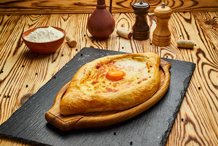 Ajarian Khachapuri traditional Georgian cheese pastry with eggs on cutting board. Homemade baking. Open pie with mozzarella
