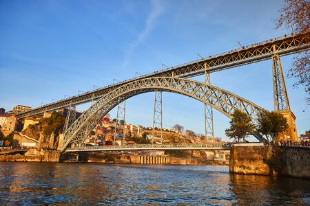 09 of December, 2018 - Porto, Portugal:  View of the historic city with the Dom Luiz bridge. A metro train can be seen on the bridge