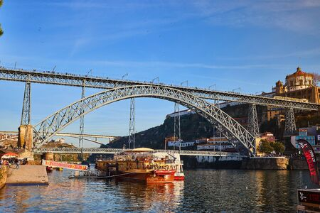 View of the historic city of Porto, Portugal with the Dom Luiz bridge. A metro train can be seen on the bridge