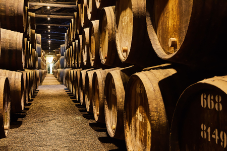Old aged traditional wooden barrels with wine in a vault lined up in cool and dark cellar in Italy, Porto, Portugal, France Редакционное