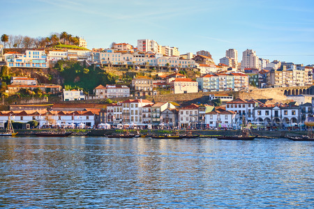 Boats on Douro river with view on  Red roofs of side Villa Nova de Gaia  in Porto. Concept of world travel, sightseeing and tourism