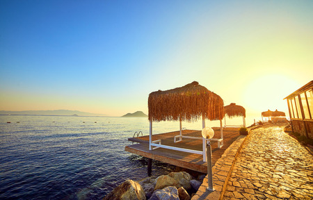 Bungalow on the sea at sunset. Wooden pavilions on the shore of a sandy beach - Bodrum, Turkey Imagens