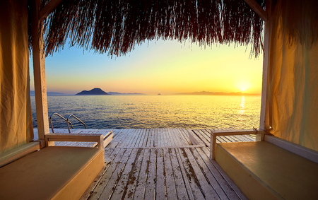 Bungalow on the sea at sunset. Wooden pavilions on the shore of a sandy beach - Bodrum, Turkey 免版税图像
