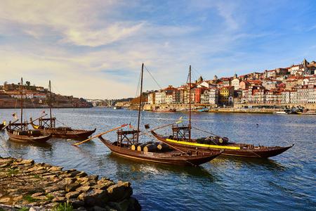 """Barcos de madera típicos portugueses, llamados """"barcos rabelos"""" que transportan barriles de vino en el río Duero con vistas a la Villa Nova de Gaia en Oporto, Portugal"""