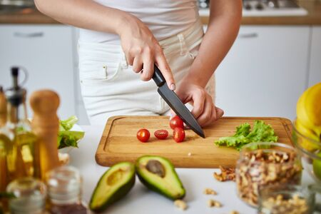 Mujer joven feliz cortando tomates para hacer ensalada en la hermosa cocina con ingredientes frescos verdes en el interior. Concepto de dieta y comida sana. Perdiendo peso