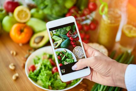 Woman hands take smartphone food photo of vegetables salad with tomatoes and fruits. Phone photography for social media or blogging. Vegan lunch, vegetarian dinner, healthy diet Stok Fotoğraf