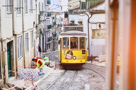 LISBONNE, PORTUGAL, 12 décembre 2018 : Tramway jaune vintage historique en bois 28 se déplaçant à travers Lisbonne, symbole de la ville. Transport indispensable pour les locaux et attraction intéressante pour les touristes