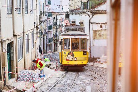 Lissabon, Portugal, 12. Dezember 2018: Holz historische Vintage gelbe Straße Straßenbahn 28 durch Lissabon, Symbol der Stadt. Unentbehrlicher Transport für Einheimische und interessante Attraktion für Touristen