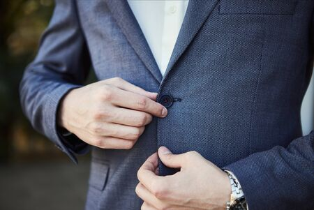 Businessman wears a jacket,male hands closeup,groom getting ready in the morning before wedding ceremony Archivio Fotografico