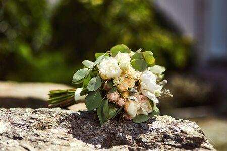 beautiful bridal wedding bouquet lying on the stone
