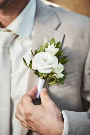 Groom corrects boutonniere on jacket close-up details