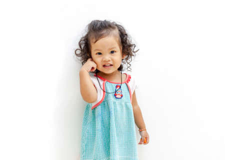 twenty two: Asian Cute girl smile with curly hair, aged twenty two months in green striped dress.