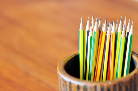 pencils in the pot on brown background photo