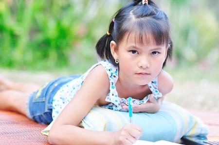 pre adolescence: Little asian girl doing homework Stock Photo