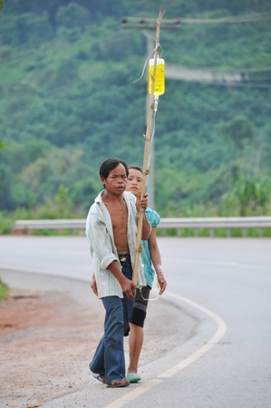 VIANGPHOUKHA,LUANGNAMTHA , LAO P.D.R -  JULY 29 : Unidentified Khmu villagers walk  home along R3A route. The man is holding a stick  hanging a saline solution bottle while the needle is still on the woman's left hand on July 29,2012,Viangphoukha,Luangnam Stock Photo - 21155562