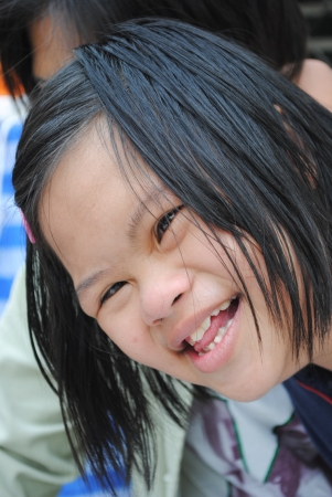 face down: UBONRATCHATHANI, THAILAND - JANUARY 19   An unidentified down syndrome girl smiles to visitors at her house on January 19, 2010 in Ubonratchathani,Thailand