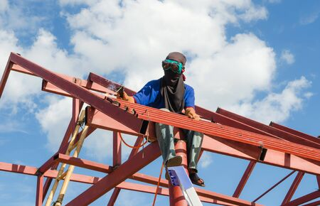 blowtorch: Authentic construction worker on scaffold using blowtorch,blue sky background  Stock Photo