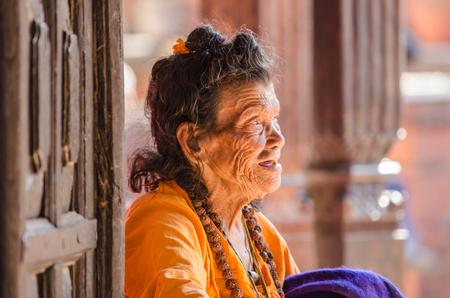 KATHMANDU, NEPAL - DECEMBER 04  An elderly woman sits at the gate of the Social welfare center Briddhashram  Elderly s home  on December 04, 2013 in Kathmandu, Nepal